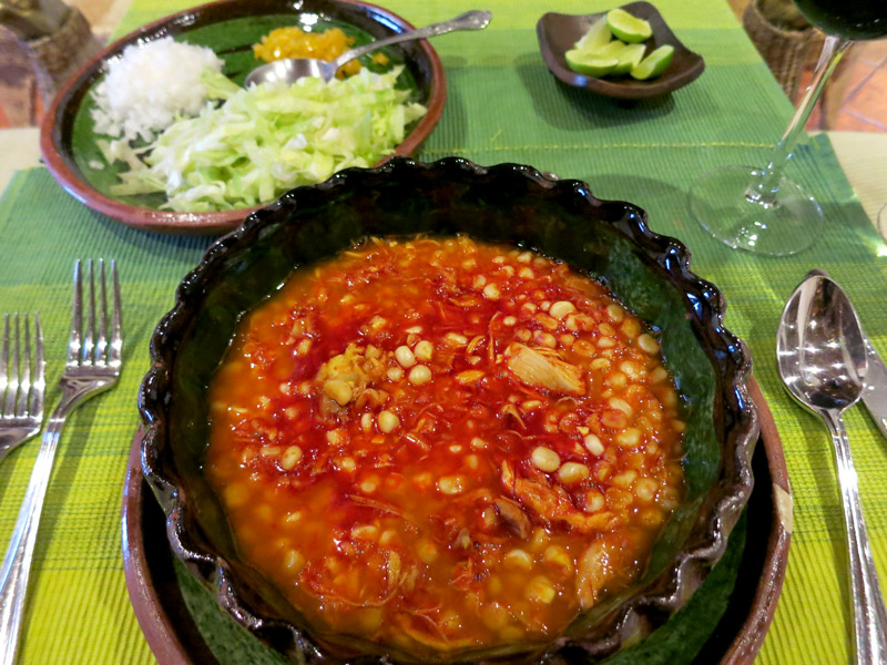 A bowl of putzuti, a traditional Purépecha soup of shredded chicken and fresh corn in a spicy, savory broth resembling pozole at Hacienda Ucazanaztacua