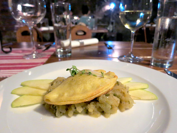 Duck liver-stuffed pasty served atop thyme-infused caramelized spring onions and crunchy apple slices at Modrá Hviezda