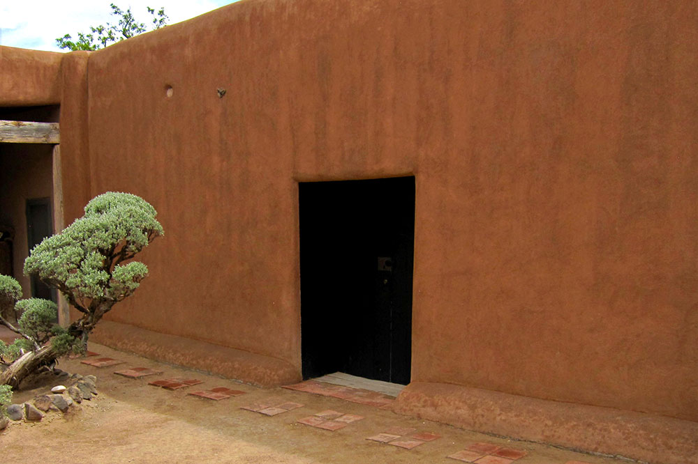 A black door in an adobe wall at Georgia O'Keeffe's studio and home in Abiquiú, New Mexico, featured in several of her paintings over the years