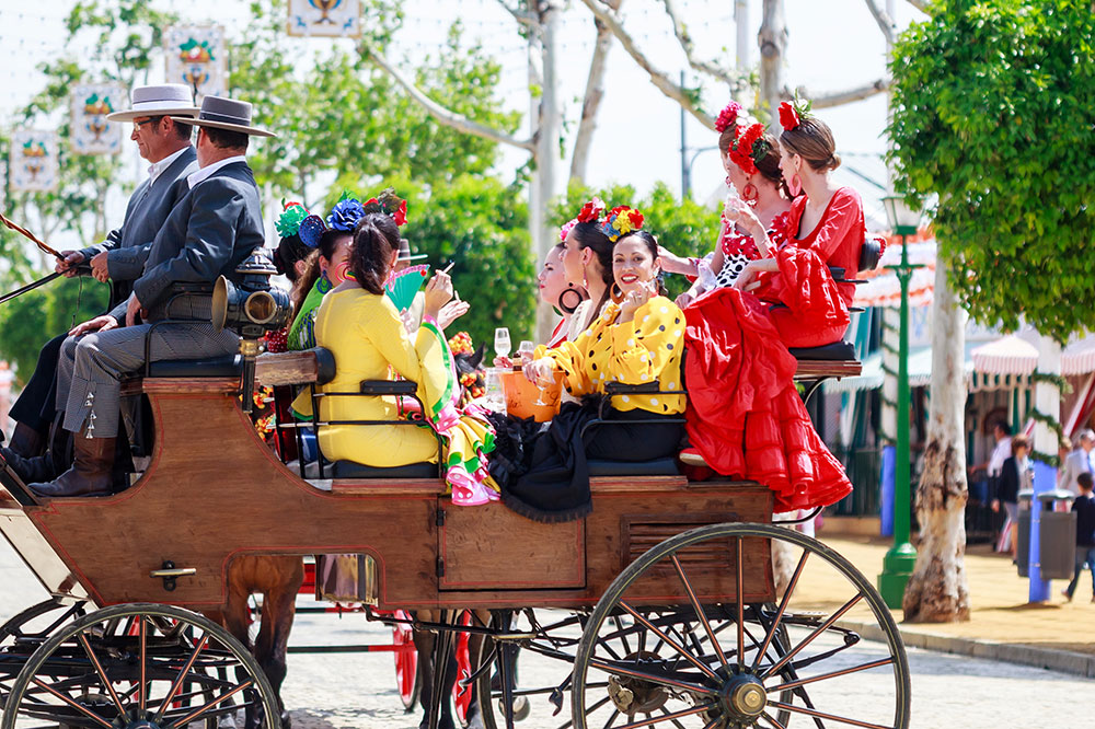 Women taking a ride in a horse-drawn carriage at April Fair in Seville, Spain