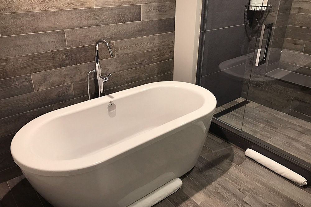 The separate tub and shower in the bath of our Queen Queen Spa Studio at the Hotel Van Zandt