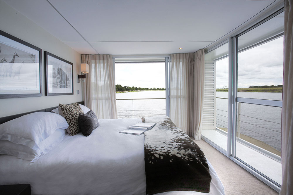 A bedroom and balcony on the <em>Zambezi Queen</em> on the Chobe River in southern Africa