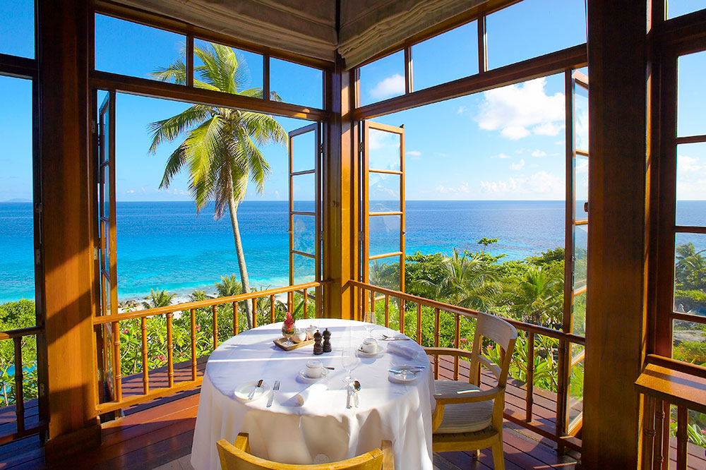 A dining table with a view of the ocean at Fregate Island Private in the Seychelles