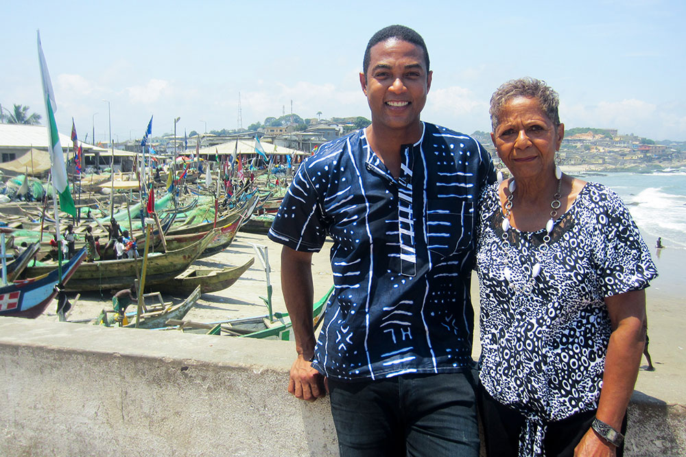 Don Lemon and his mother in front of fishing boats on Elmina Beach in Cape Coast, Ghana.