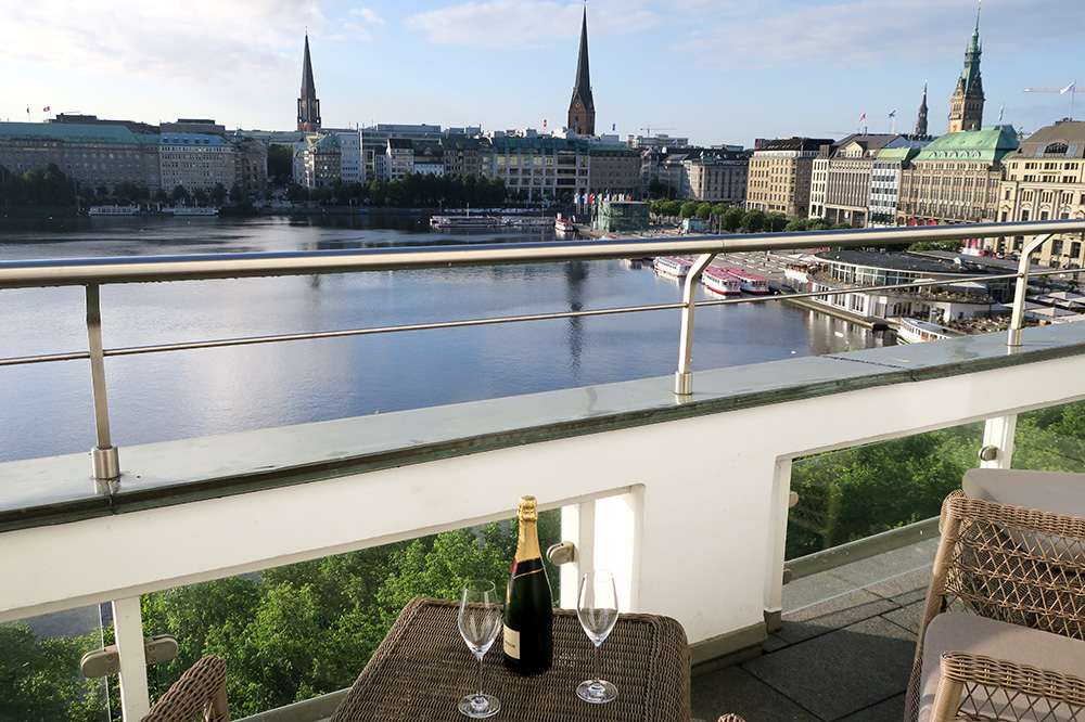 Enjoying champagne with a view on the terrace of our Deluxe Double Room Lakeview with Balcony at the Fairmont Hotel Vier Jahreszeiten - Photo by Hideaway Report editor