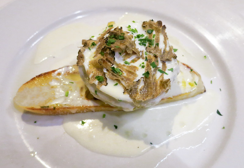 Artichoke bruschetta topped with a poached egg, Parmesan cream, shaved black truffle and truffle oil at <i>Ellina</i> - Photo by Hideaway Report editor