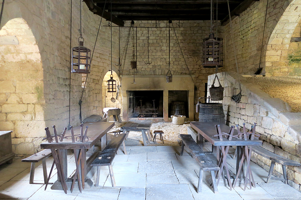 The kitchen, decorated with large hanging lanterns and tables with built-in sword holders, at Château de Beynac in the Dordogne, France - Photo by Hideaway Report editor