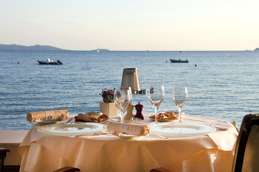 A dining table with a view at <em>La Virile Fontaine</em> at Le Club de Cavalière & Spa in Le Lavandou, France