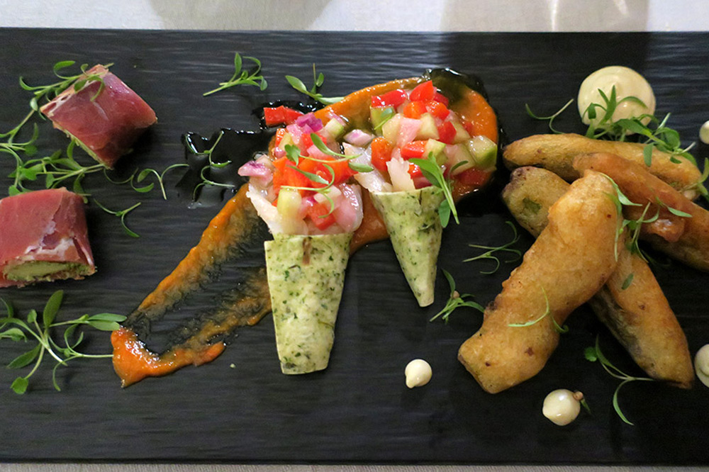 Portuguese tapas (from left: pata negra ham wrapping Azorean Ilha cheese and parsley pesto, cones of smoked cod, and sugar-pea tempura) at <em>Sítio</em> restaurant at the Valverde Hotel
