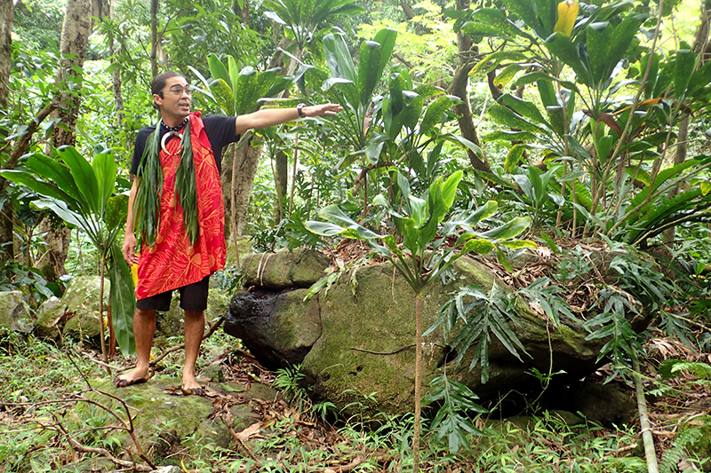 Greg Kawaimaka Solatorio beside the altar stone of a heiau at Halawa Valley, Molokai - Photo by Hideaway Report editor
