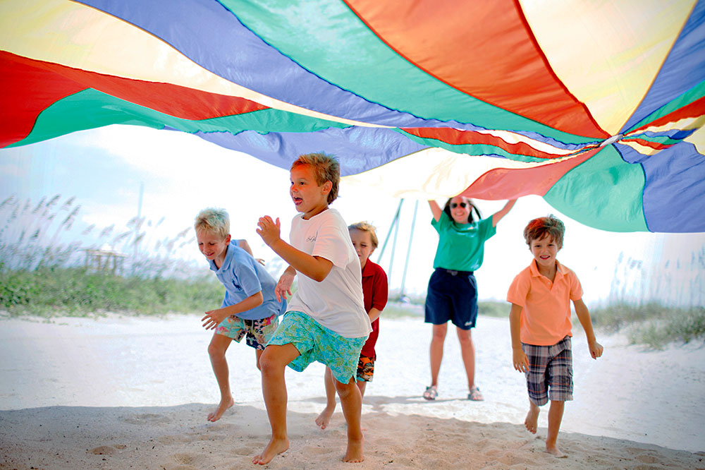 Kids playing under a parachute at The Cloister at Sea Island's Camp Cloister
