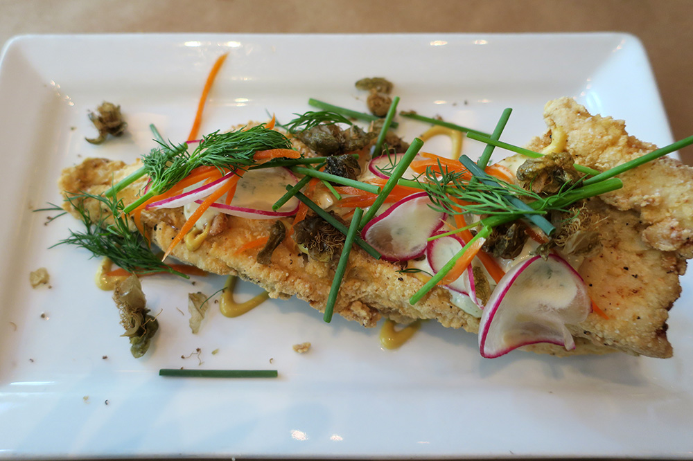 Chicken-fried trout with fried caper flowers, radish slices, chives and pickled carrots from <em>Little Bird</em> in Portland, Oregon - Photo by Hideaway Report editor