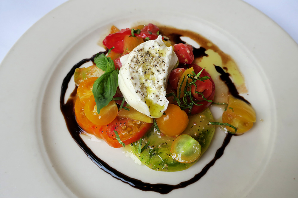 Heirloom tomatoes and burrata with basil, balsamic vinegar and garlic-infused olive oil from Higgins in Portland, Oregon