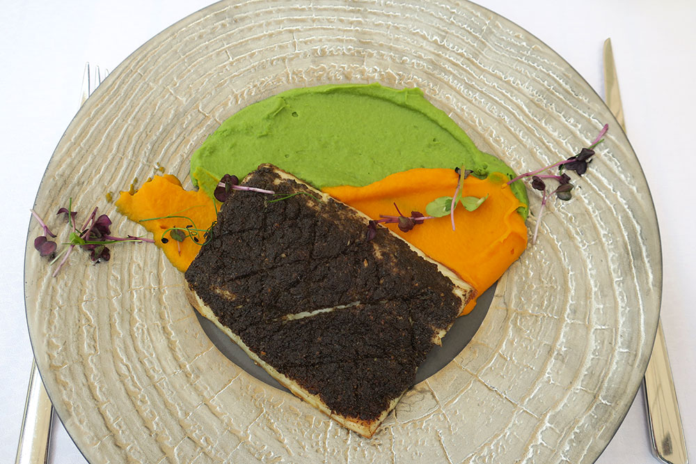 Olive tapenade-crusted sea bass with purées of carrots and peas from <em>Proto Fish Restaurant</em>