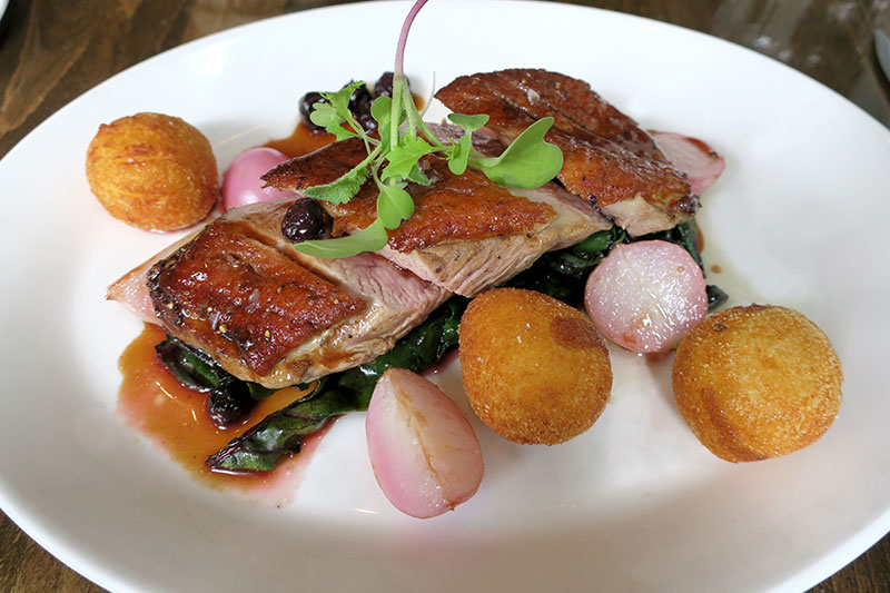 Duck breast with a blueberry-mustard jus and pommes dauphine (potato puffs) at Tableau Bar Bistro - Photo by Hideaway Report editor